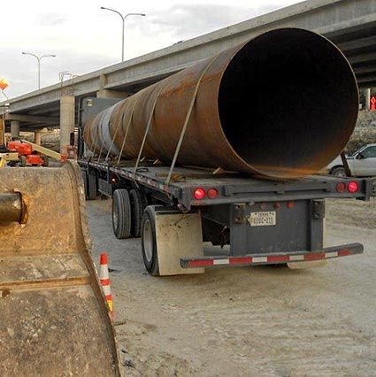 Road Bore Casing Pipe on semi-truck trailer near highway